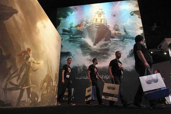 People pass exhibit artwork, including World of Warships, on the first day of E3 in Los Angeles, California.