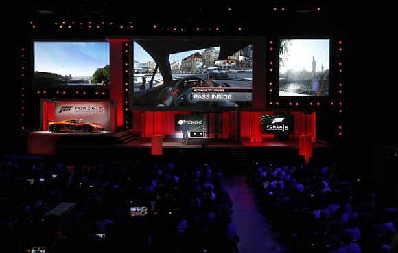 Attendees watch scenes from the game Forza Motorsport 5 during the Xbox E3 Media Briefing at USC's Galen Center in Los Angeles, California.