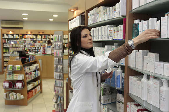 Christina Georgiadou, who is a trained nurse and employee of the pharmacy, arranges a display in Oreokastro, a suburb of Thessaloniki in northern Greece.