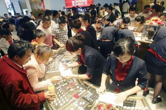 Customers look at gold accessories at a gold store in Jinan, Shandong province.