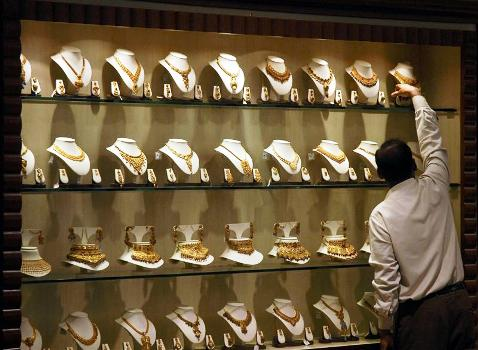 A salesman arranges gold necklaces at a jewellery showroom in Chennai.