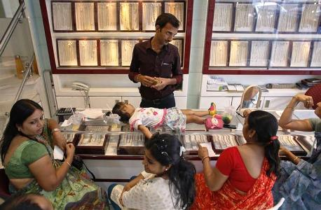An employee counts money, as a child lies on the counter, following purchases of gold jewellery inside a showroom in Mumbai.