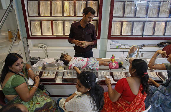 An employee counts money, as a child lies on a counter, inside a showroom in Mumbai.