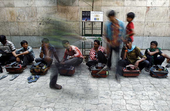A commuter walks past cobblers sitting in a line waiting for customers outside a metro station in New Delhi.