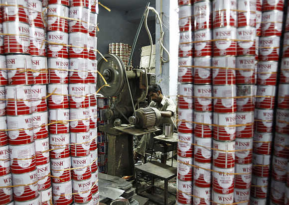 A labourer works inside the tin cans manufacturing unit at a factory in New Delhi.