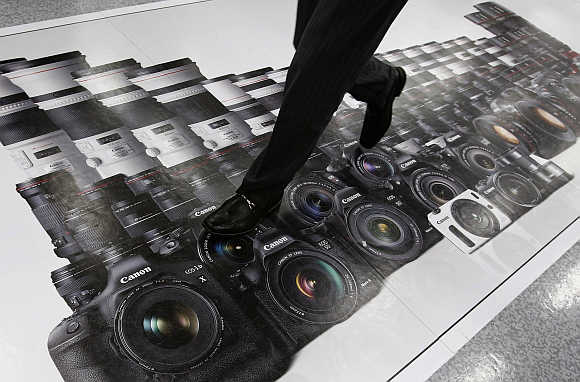 A man walks on an advertisement of Canon digital cameras at an electronics retail store in Tokyo, Japan.