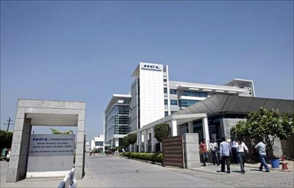 People walk in front of the HCL Technologies Ltd office at Noida, on the outskirts of New Delhi