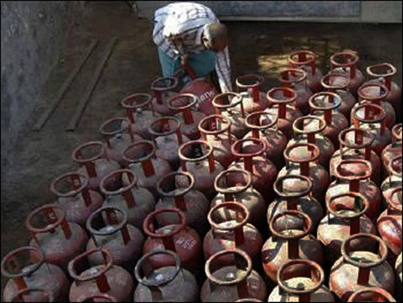 A worker collects LPG gas cylinders.