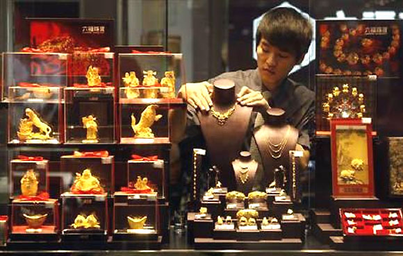 An employee adjusts a gold necklace on a displaying model near glass cases containing figurines at a shop in Wuhan, Hubei province.