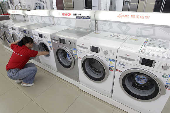 A sales assistant cleans a washing machine at an electrical appliance shop in Wuhan, Hubei province, China.
