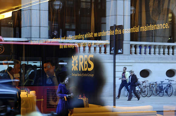 Pedestrians are reflected in the window of a Royal Bank of Scotland building in the City of London.
