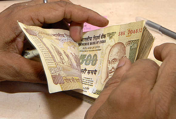 A cashier counts rupee notes inside a bank in Lucknow.