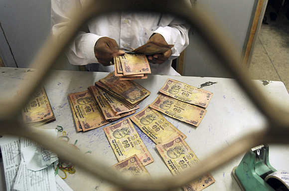 An employee sorts rupee notes at a cash counter inside a bank in Agartala, Tripura.