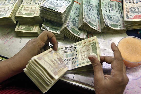 An employee counts rupee notes at a cash counter inside a bank in Kolkata.