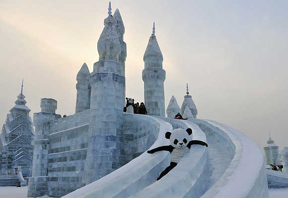 An employee wearing a panda costume slides down from an ice sculpture during the Harbin International Ice and Snow World festival in Harbin, Heilongjiang province, China.