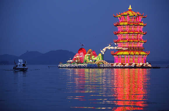 A tourist boat rows past a group of lanterns, featuring the Yellow Crane Tower, during the lighting test period of the Wuhan-Chengdu International Panda Lantern Festival on Donghu lake in Wuhan, Hubei province.