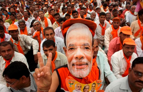 A BJP supporter wears a Narendra Modi mask at a rally.