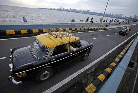 A Premier Padmini taxi travels along Marine Drive in Mumbai.