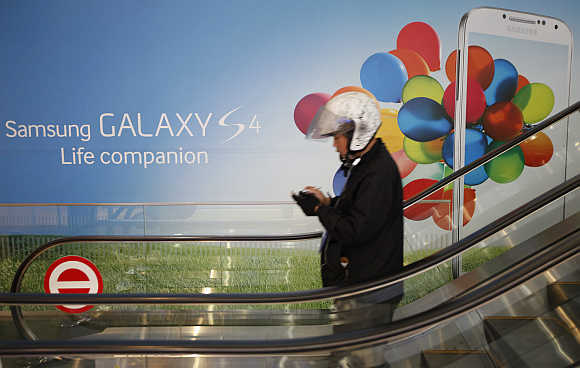 A motorcycle dispatch rider uses his smartphone next to an advertisement promoting Samsung Galaxy S4 smartphone at the company's headquarters in Seoul, South Korea.