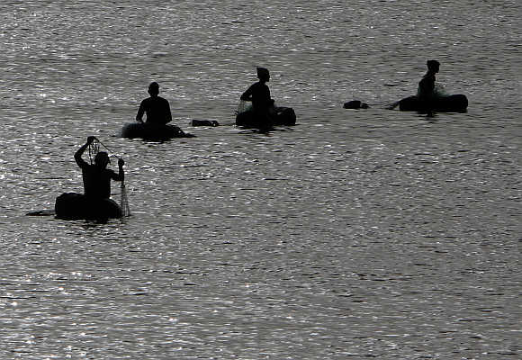 Fishermen floating on rubber air tubes are silhouetted as they catch fish in the waters of the Sabarmati river in Ahmedabad.