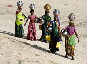 Women carrying empty pitchers walk to draw water from a well. Photograph: Reuters