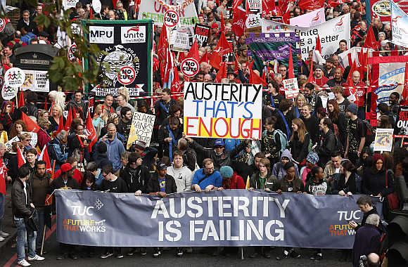 Demonstrators hold placards before the start of a protest march organised by the Trades Union Congress in central London.