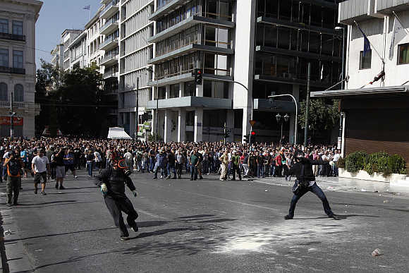 Demonstrators throw objects at riot police at an anti-austerity march in central Athens, Greece.