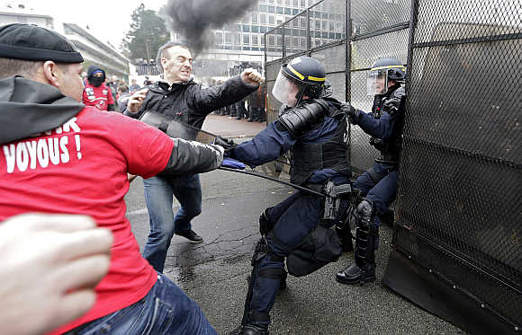 Protestors scuffle with French CRS riot police in front of tyre maker Goodyear Dunlop France headquarters during a demonstration against job cuts in Rueil Malmaison, near Paris.