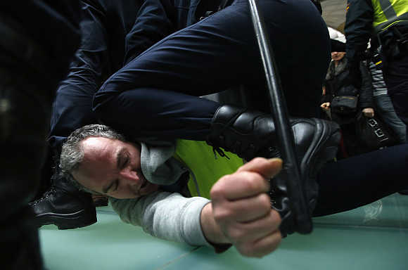 An Iberia worker is arrested by Spanish riot police officer during clashes at Madrid's Barajas airport.