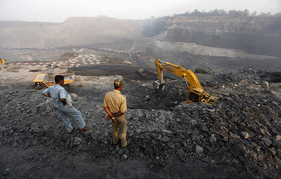 A policeman and a worker watch coal being loaded on a truck in the Mahanadi coal fields, near Talcher town, in Orissa.