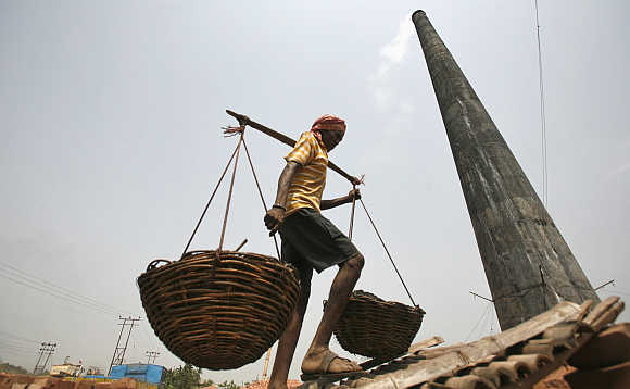 A worker carries coal in baskets at a wholesale coal shop on the outskirts of Agartala, capital of Tripura.