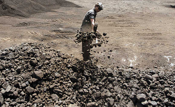 A worker shovels coal at a yard in Ahmedabad.