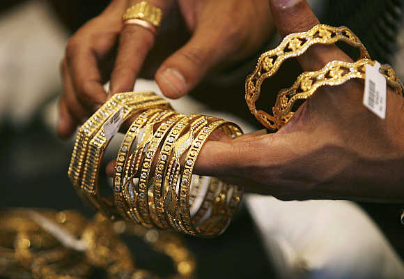 A shopkeeper shows gold bangles to a customer at a jewellery shop in Mumbai.