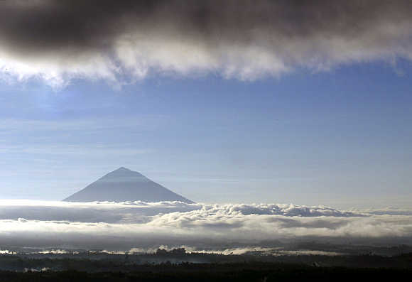 Peak of Gunung Agung rises above the clouds in eastern Bali.