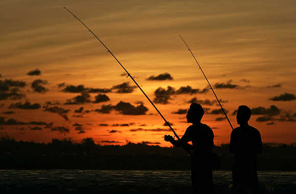 Anglers fish at sunset off Legian beach on the Indonesian resort island of Bali.