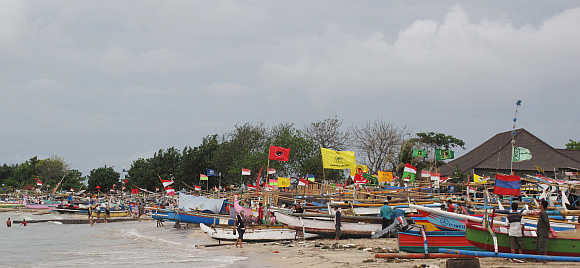 Boats rest on a beach in the fishing village of Jimbaran, Bali.