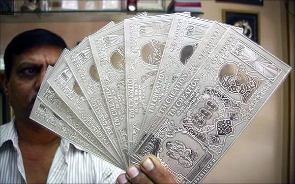 jeweller displays silver plates in the form of Indian rupee notes in Chandigarh.