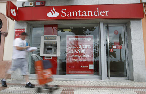 A postman walks pass a Santander's bank office in El Masnou, near Barcelona, Spain.