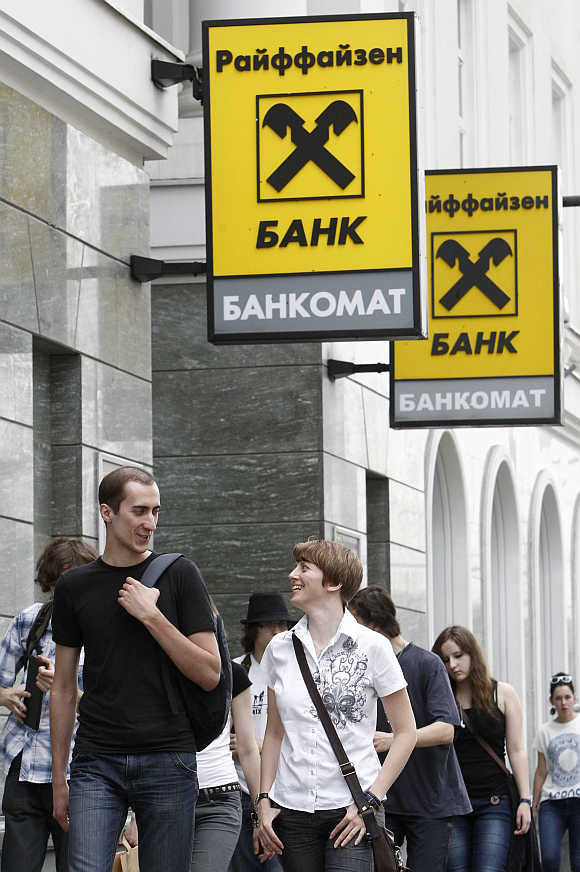 Pedestrians walk past a Raiffeisen Bank branch in Moscow.