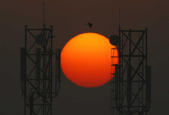 Sun rises over telecommunication towers in New Delhi.