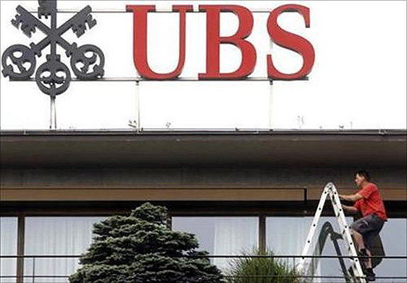 A worker climbs on a ladder under the logo of Swiss bank UBS at the company's