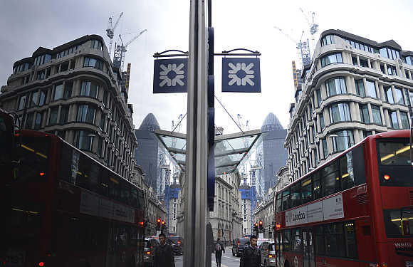 Logo of Royal Bank of Scotland branch is reflected on a window in the City of London.