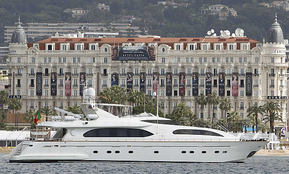 A yacht cruises past the Carlton Hotel in Cannes, France.