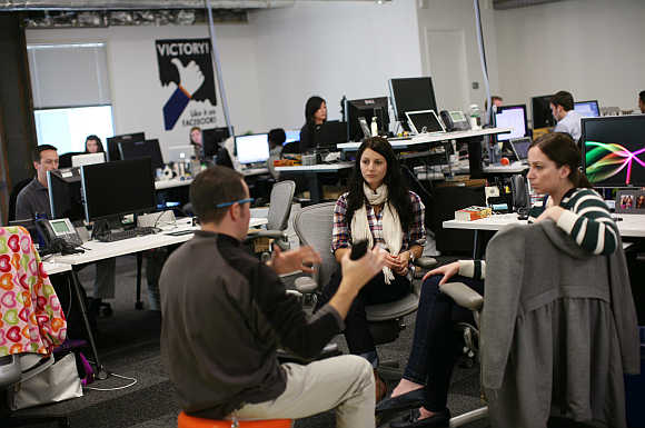 Employees gather in their work environment for a discussion at the headquarters of Facebook in Menlo Park, California.