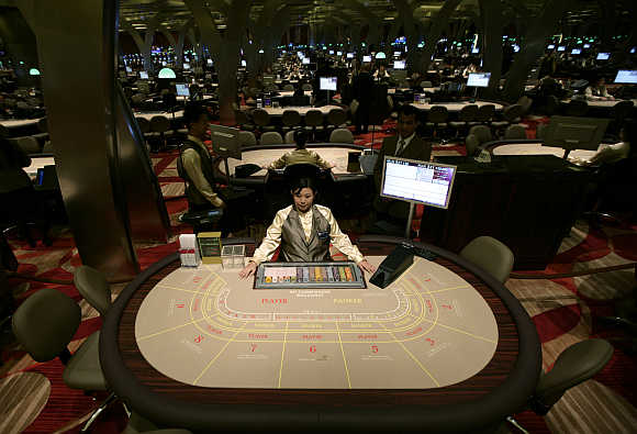 A croupier waits for gamblers at a table inside the Marina Bay Sands casino in Singapore.
