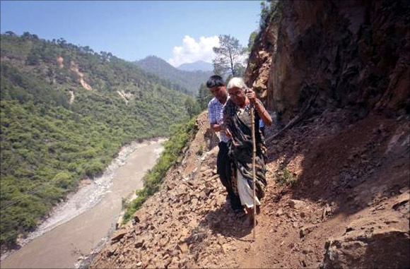 A pilgrim is helped by a villager as she tries to cross on a pathway damaged by landslide in Rudraprayag in Uttarakhand.