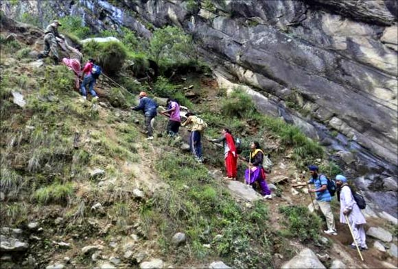 Pilgrims are helped to climb over a hill by Army soldiers during a rescue operation at Govindghat in Uttarakhand.