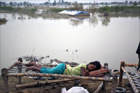A displaced girl sleeps outside her makeshift tent at a camp by the roadside after a rise in the waters of the river Yamuna after heavy rains in New Delhi