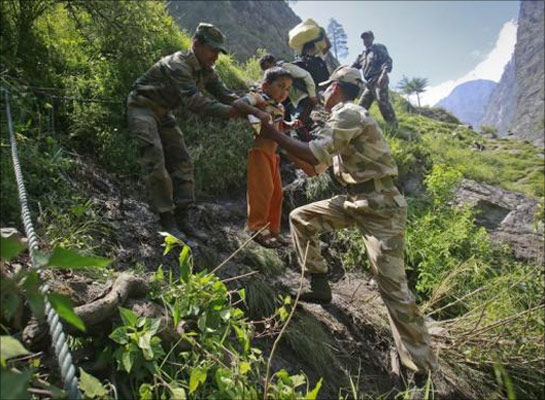 A child is carried by soldiers to help him climb down a hill during a rescue operation at Govindghat in Uttarakhand.