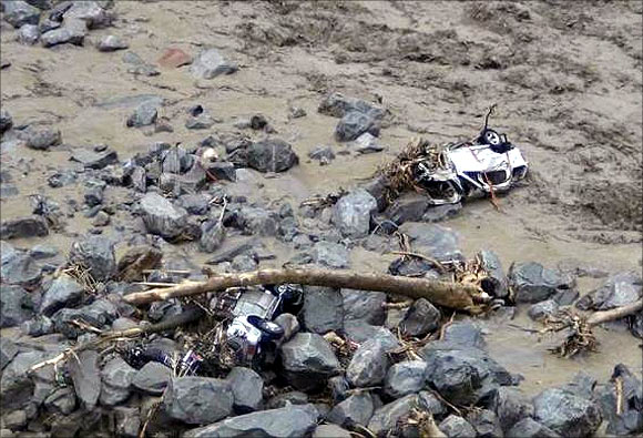 Vehicles are pictured in the flooded waters of a stream after heavy rains in Uttarakhand.